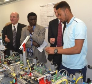 Inside Camden County College's mobile manufacturing classroom, a student demonstrates the use of mechatronics technology to (from left) Ray Vaccari of NJIT, Cumberland County College President Thomas Isekenegbe and Aaron Fichtner, deputy state labor commissioner, during the Consortium's 10th anniversary event