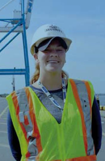 Holt Training Coordinator Dotty Foltz stands in front of a giant container crane at the ship terminal.